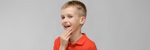Портрет маленького белокурого счастливого усмехаясь кавказского мальчика в оранжевой футболке с рукой около его стороны на серой  стоковая фотография