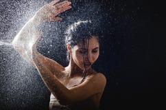 Портрет маленькой девочки и брызгать вода в ее стороне красивая женская модель на черной предпосылке стоковое изображение