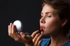 Портрет маленькой девочки на черной предпосылке которая красит ее губы с красной губной помадой Стоковая Фотография RF