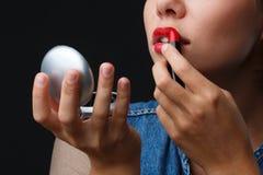 Портрет маленькой девочки на черной предпосылке которая красит ее губы с красной губной помадой Стоковые Фотографии RF