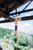 Портрет маленькой девочки невесты с профессиональным макияжем свадьбы и hairdo в окне стоковые изображения