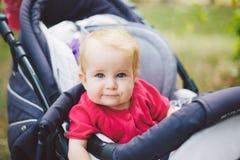 Портрет маленькой смешной девушки ребенка белокурой при голубые глазы сидя в детской сидячей коляске в лете для зеленых цветов Tr Стоковое Фото