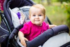 Портрет маленькой смешной девушки ребенка белокурой при голубые глазы сидя в детской сидячей коляске в лете для зеленых цветов Tr Стоковая Фотография RF