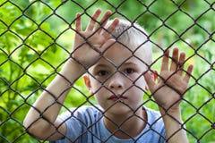 Портрет мальчика за загородкой звена цепи Стоковая Фотография RF