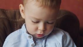 Портрет мальчика сидя на кресле и играх с игрушками сток-видео