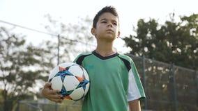 Портрет мальчика спорта с футбольным мячом в руке идя на поле акции видеоматериалы