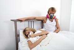 Портрет маски противогаза человека нося пока женщина страдая от холода в кровати стоковые фото