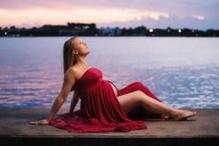 Портрет материнства красного цвета женщины нося стоковая фотография
