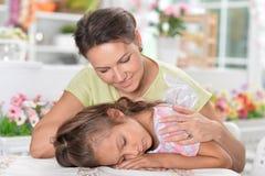 Портрет матери будя дочь которая спать на таблице стоковое изображение