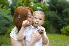 Портрет матери и ее четырёхлетнего сына outdoors Стоковые Изображения RF