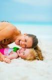 Портрет матери и ребёнка играя на пляже стоковые фотографии rf