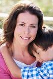 Портрет матери и сына обнимая Outdoors Стоковое Изображение