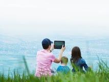 Портрет матери семьи держа ПК, брата и сестру таблетки совместно сидя в природе Стоковые Фотографии RF