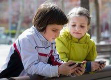 Портрет маленьких девочек играя с телефонами Стоковая Фотография
