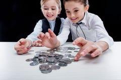 Портрет маленьких девочек сидя на таблице и расчетливых деньгах Стоковые Фото