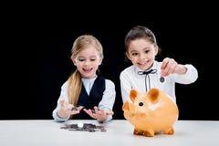 Портрет маленьких девочек сидя на таблице и расчетливых деньгах Стоковое Изображение
