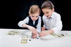 Портрет маленьких девочек сидя на таблице и расчетливых деньгах Стоковое Изображение RF