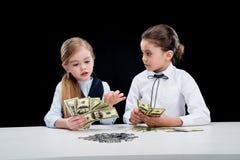 Портрет маленьких девочек сидя на таблице и расчетливых деньгах Стоковая Фотография RF
