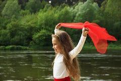 Портрет маленького милого танца девушки с красным шарфом рекой Стоковое Фото