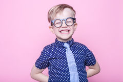 Портрет маленького усмехаясь мальчика в смешных стеклах и связи школа preschool Способ Портрет студии над розовой предпосылкой стоковые фотографии rf