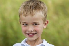 Портрет маленького усмехаясь мальчика с золотыми белокурыми волосами i соломы Стоковое Изображение