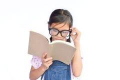 Портрет маленькой азиатской девушки читая книгу на белизне Стоковые Фотографии RF