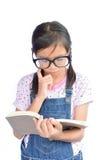 Портрет маленькой азиатской девушки читая книгу на белизне Стоковые Изображения RF