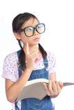 Портрет маленькой азиатской девушки читая книгу на белизне Стоковое фото RF