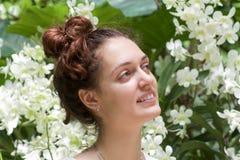 Портрет маленькой девочки без состава смотря белые орхидеи Стоковая Фотография