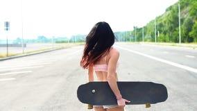 Портрет маленькой девочки битника усмехаясь с longboard движение медленное акции видеоматериалы