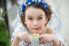 Портрет маленькой девочки в кофе флористического платья выпивая Стоковые Изображения RF