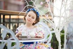Портрет маленькой девочки в чае флористического платья выпивая Стоковые Фотографии RF