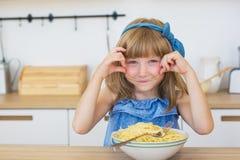 Портрет маленькой девочки смешной ест спагетти от блюда и усмехаться Стоковые Фото