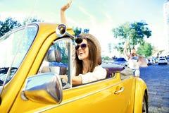 Портрет маленькой девочки управляя cabriolet на заходе солнца Стоковое Изображение