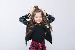 Портрет маленькой девушки битника в куртке бомбардировщика показывая рожки руками представлять Курчавый современный стиль причёсо Стоковое Фото