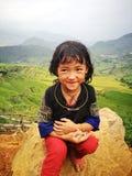Портрет маленькой девушки меньшинства Hmong (Miao) сидя на утесе Стоковая Фотография