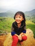 Портрет маленькой девушки меньшинства Hmong (Miao) сидя на утесе Стоковое Изображение RF