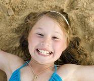 Портрет маленькой милой девушки на песке имея потеху Стоковая Фотография