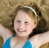 Портрет маленькой милой девушки на песке имея потеху Стоковые Фото