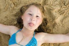 Портрет маленькой милой девушки на песке имея потеху Стоковые Изображения