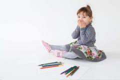 Портрет маленькой excited девушки сидя и играя с красочными crayons Стоковое Фото