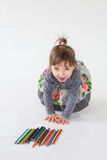 Портрет маленькой excited девушки сидя и играя с красочными crayons Стоковые Фото