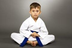 Портрет мальчика в тренировке кимоно на поле Стоковые Фотографии RF