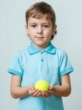 Портрет мальчика держа теннисный мяч в руках Стоковое Фото