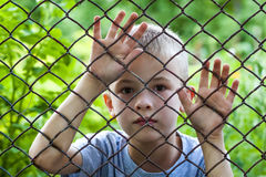 Портрет мальчика за загородкой звена цепи Стоковое Изображение RF