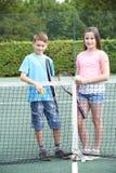 Портрет мальчика и девушки играя теннис совместно Стоковое Изображение