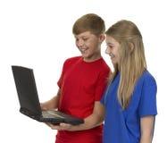 Портрет мальчика и девушки смотря компьтер-книжку Стоковое фото RF
