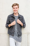 Портрет мальчика подростка усмехаясь стоя над конкретной предпосылкой Стоковая Фотография RF