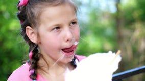 Портрет, милая девушка 8 лет, блондинка, с веснушками, и пестроткаными отрезками провода, ест сладостный белый хлопок, хлопок сток-видео