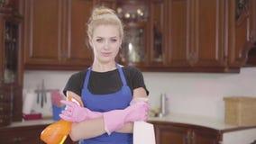 Портрет миленькая молодая женщина, стоящая на кухне с скрещенными руками держащая бутылки моющего средства, глядя в камеру видеоматериал
